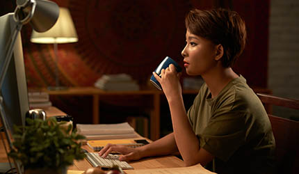 Female drinking coffee and looking at computer
